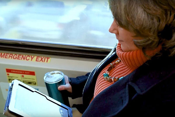 SunRail Rider Story - Kelly - female rider sitting by window on the train reading a tablet with a coffee in hand