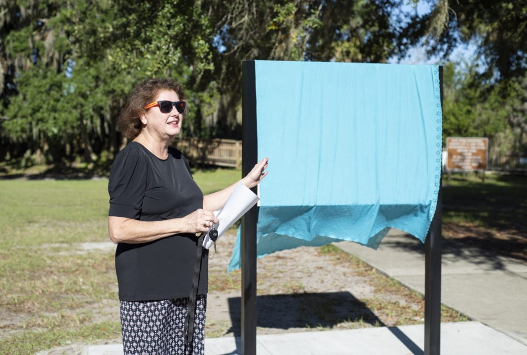 Cindy Sullivan, Chair of River of Lakes Heritage Corridor, prepares the group for the unveiling.